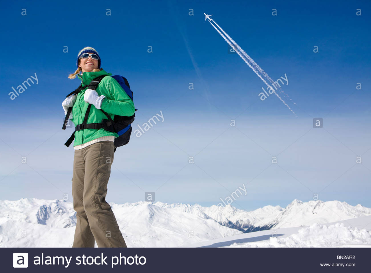 Airplane flying over woman backpacking on snowy mountain - Stock Image