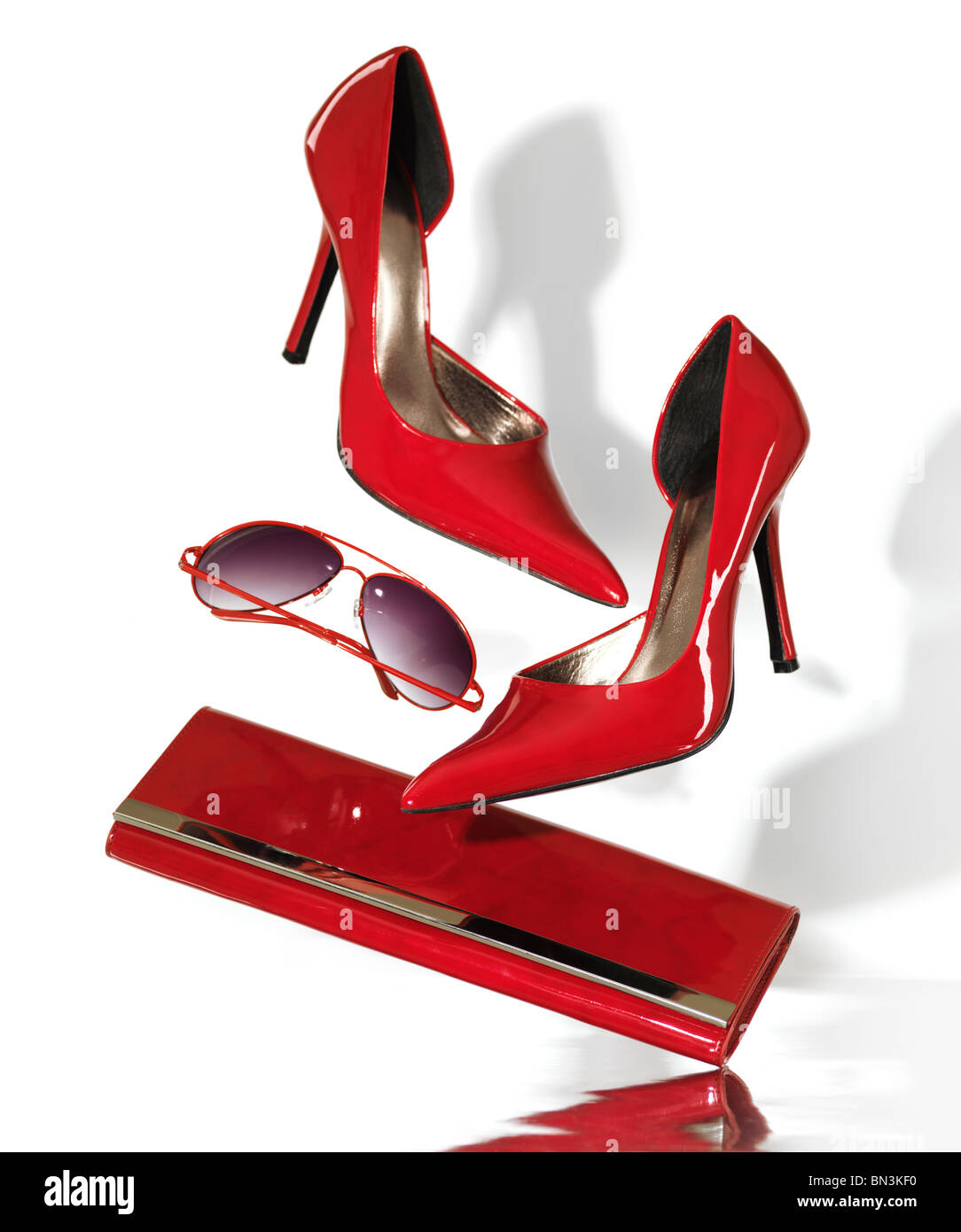 Stylish red high heel stiletto shoes sunglasses and a clutch hand bag falling on metal surface isolated on white Stock Photo