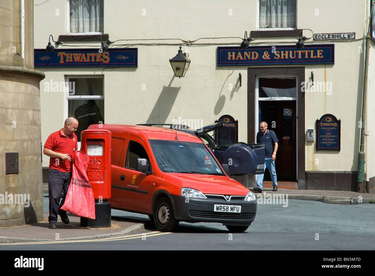 Postman emptying post-box in front of Hand & Shuttle pub, Padiham, Lancashire, England UK Stock Photo