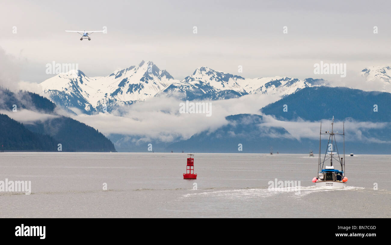 A floatplane flies down Gastineau Channel as gillnetters head to the fishing grounds in Taku Inlet near Juneau, - Stock Image