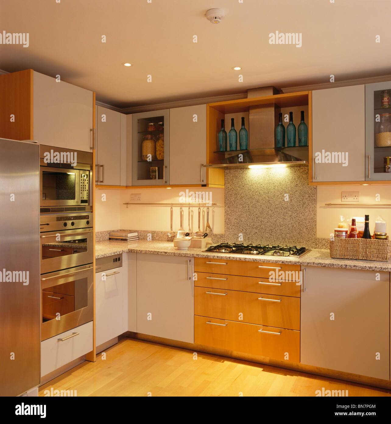 Recessed Lighting Below Fitted Wall Cupboards In Modern White Kitchen With  Baulthaup Oven And With Granite Splash Back Above Hob