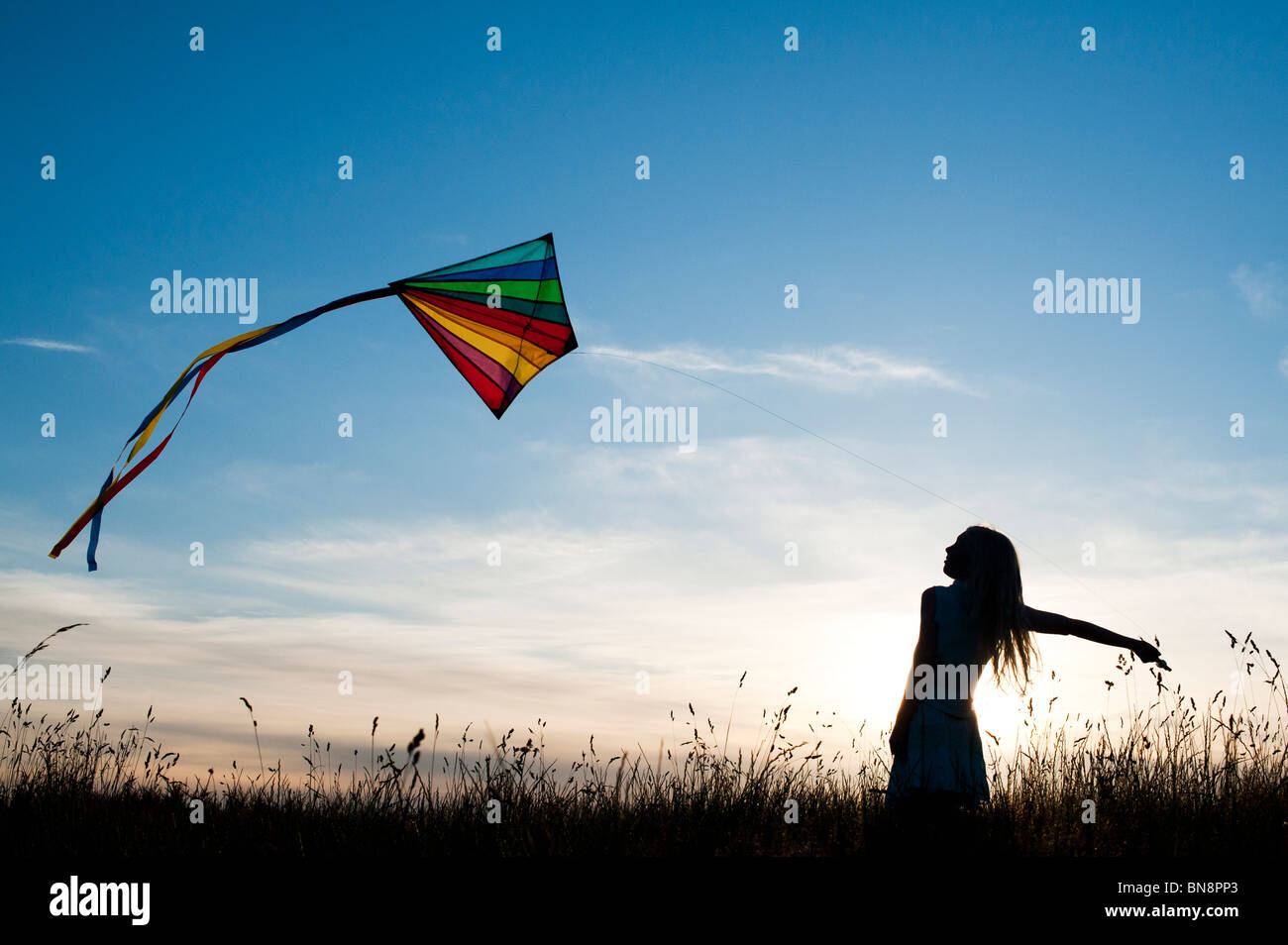 Young Girl having fun flying a multicoloured kite in the English countryside. Silhouette - Stock Image