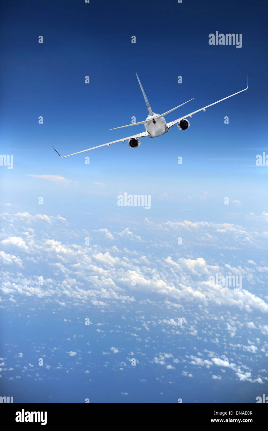 Jet airliner in flight with clouds in the distance - Stock Image