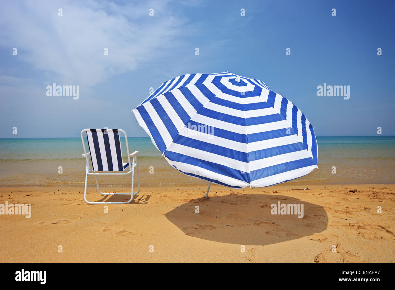 An umbrella and a chair on a sandy beach - Stock Image