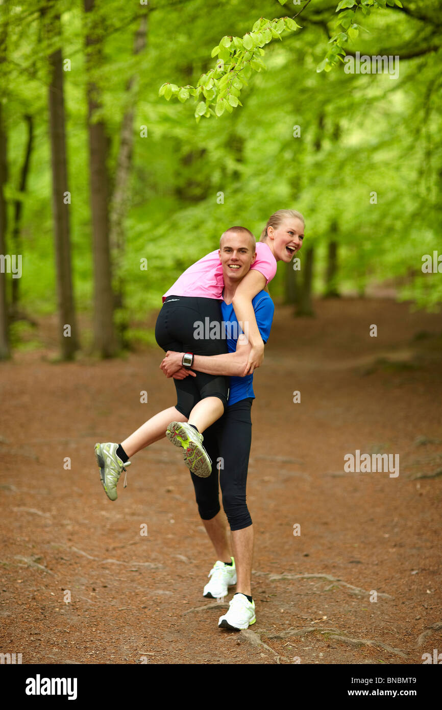 Couple running in forest, having fun - Stock Image