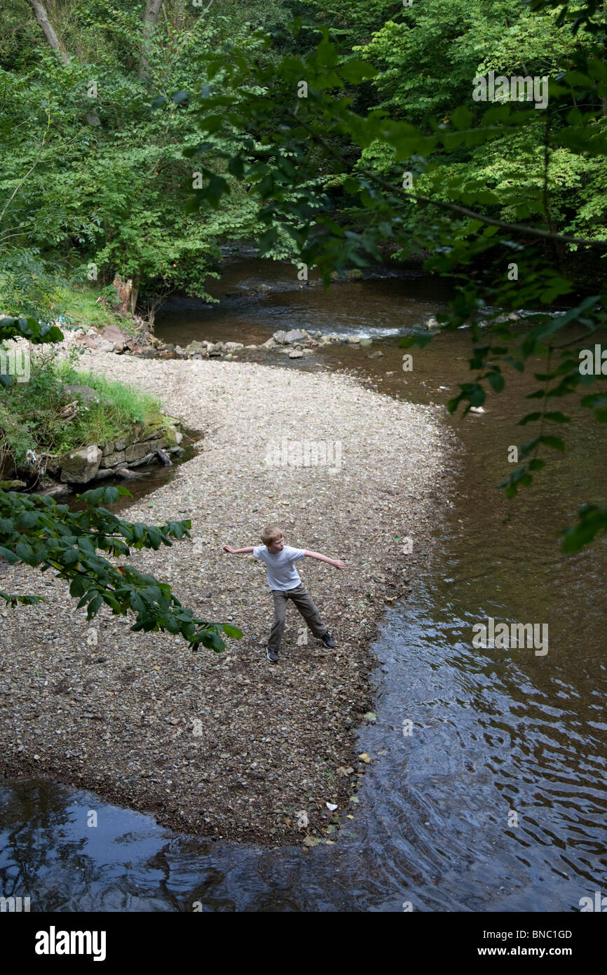 Young boy throwing stones in the River Alyn. - Stock Image