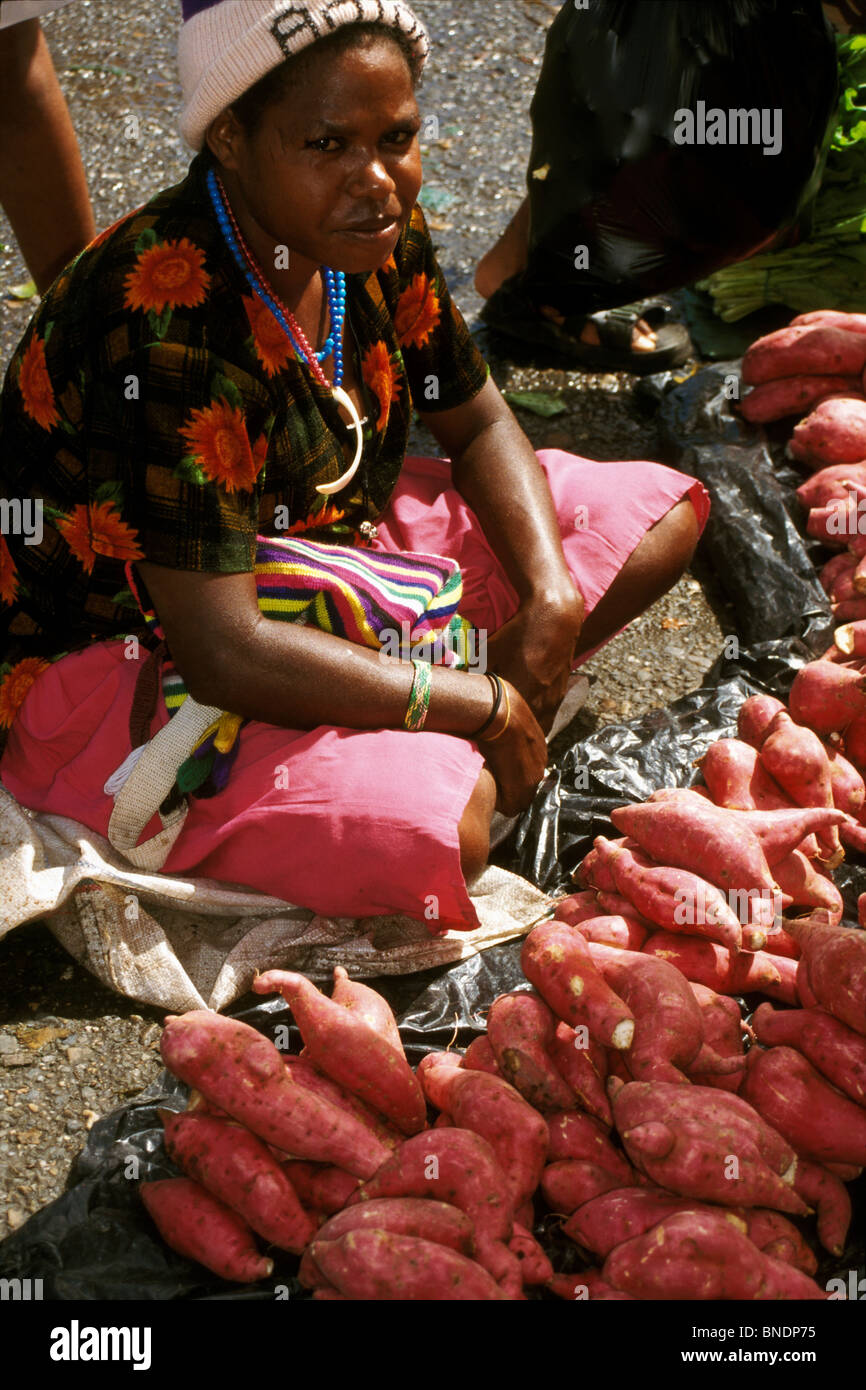 Papuan woman selling tubers in the market at Timika, West Papua (Irian Jaya), Indonesia - Stock Image