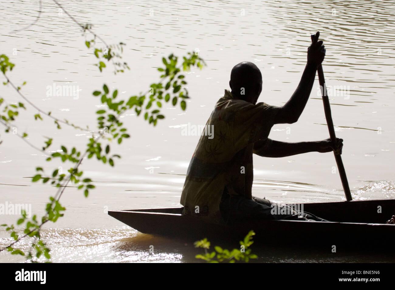 Fisherman cautiously passes the hippos in the Black Volta, Wechiau Community Hippo Sanctuary, near Wa, Ghana. - Stock Image