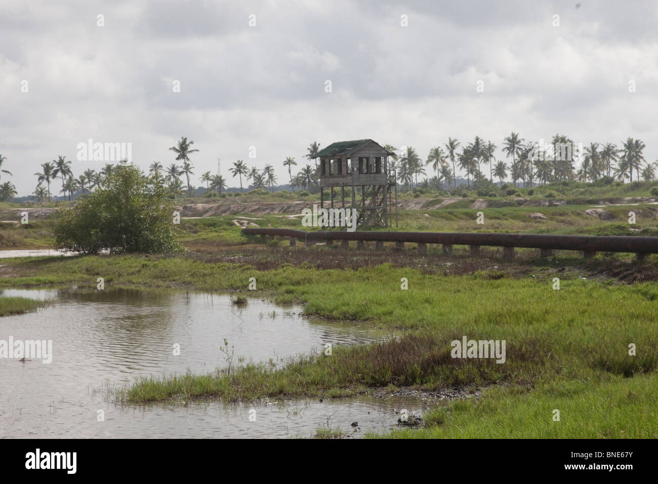 Pipeline carrying seawater into pans in the Muni lagoon, near Winneba, Ghana, for the production of salt. - Stock Image