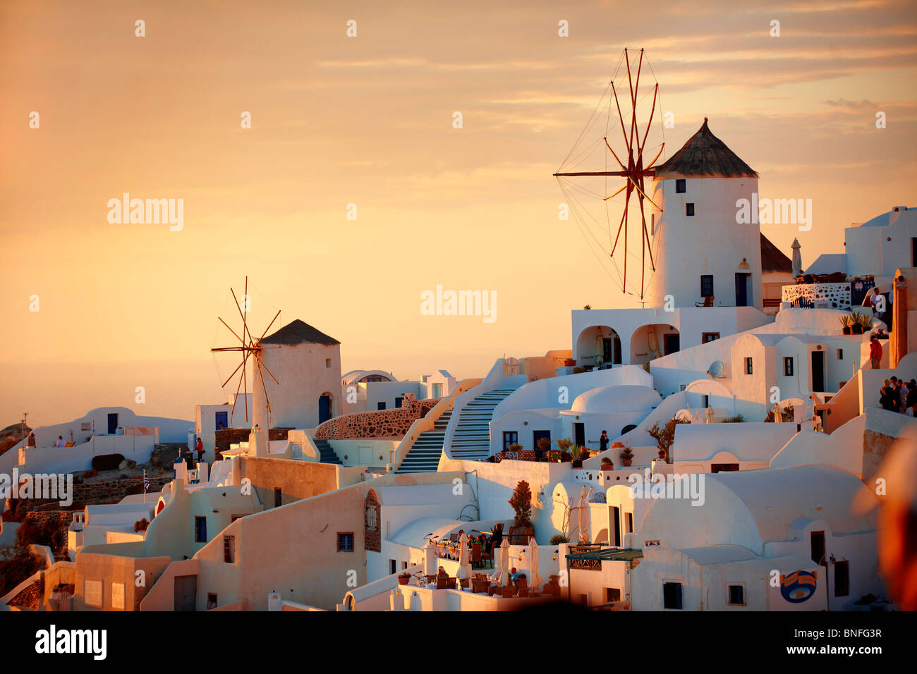 Oia ( Ia ) Santorini - Windmills and town at sunset, Greek Cyclades islands - Photos, pictures and images - Stock Image