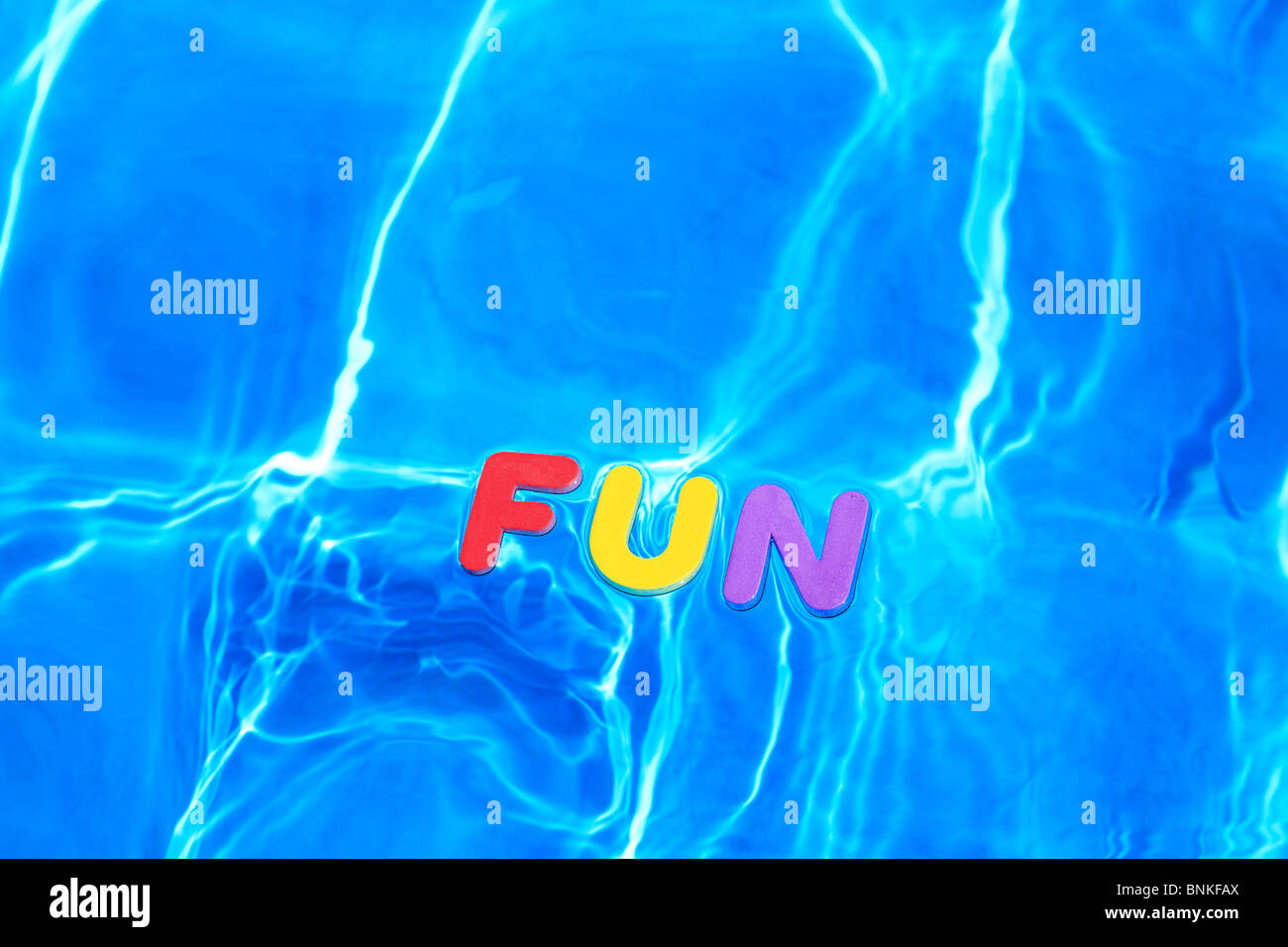 The word FUN made from foam letters floating on the water surface of a swimming pool - Stock Image