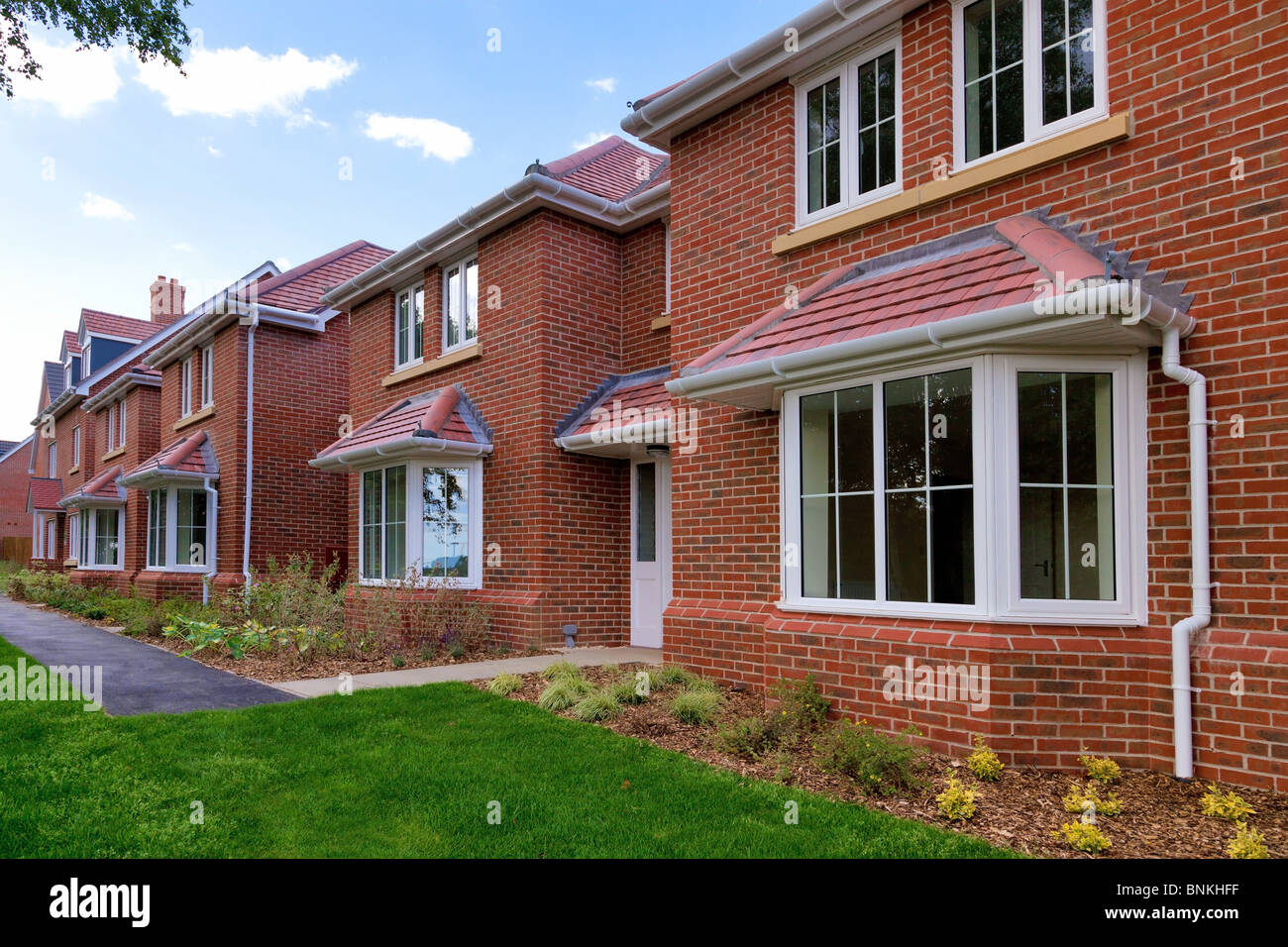 Photo of a row of brand new empty houses for sale on a housing development. - Stock Image