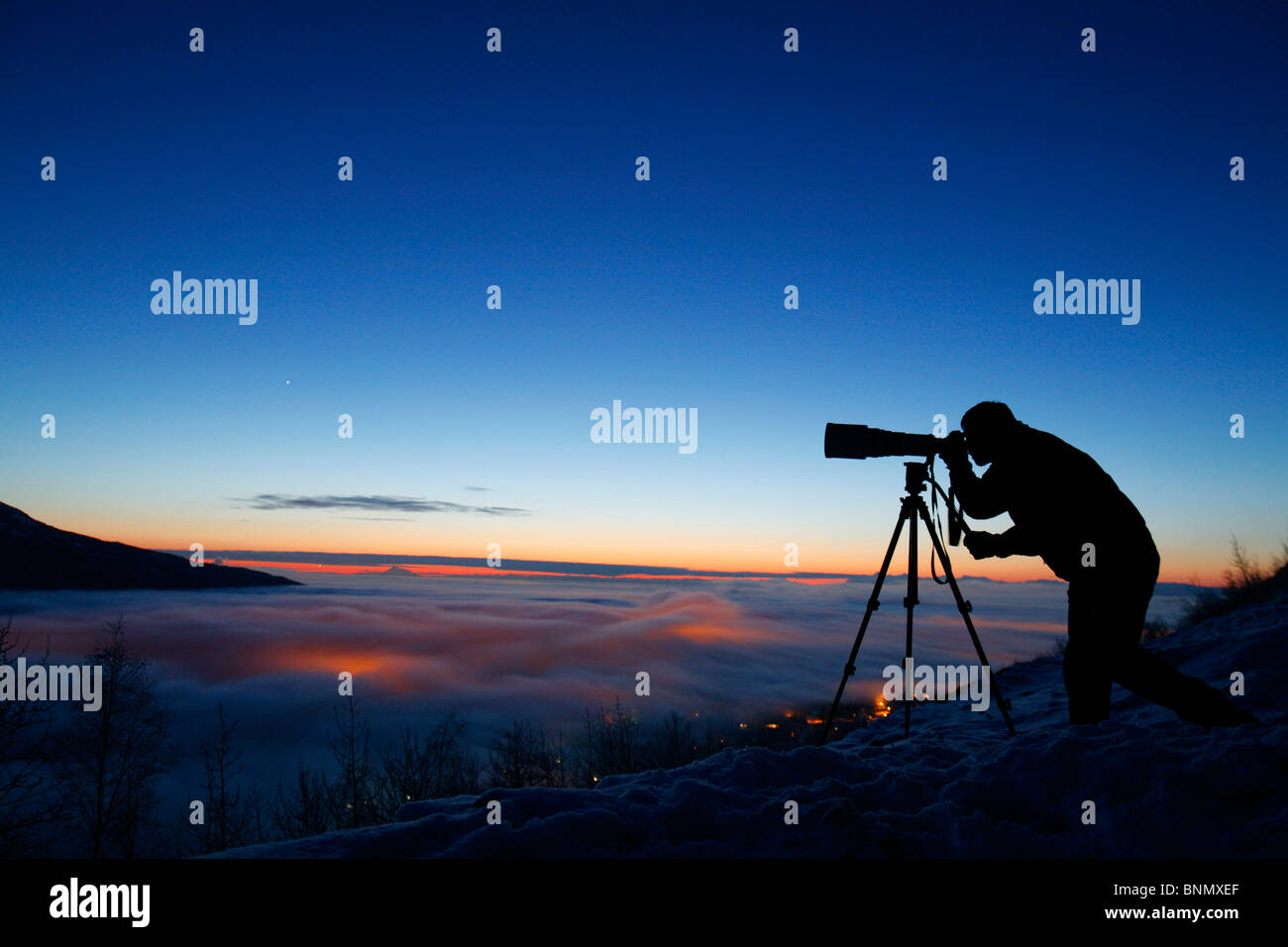 Silhouette of photographer at sunset in Eagle River Valley, Alaska, Winter - Stock Image