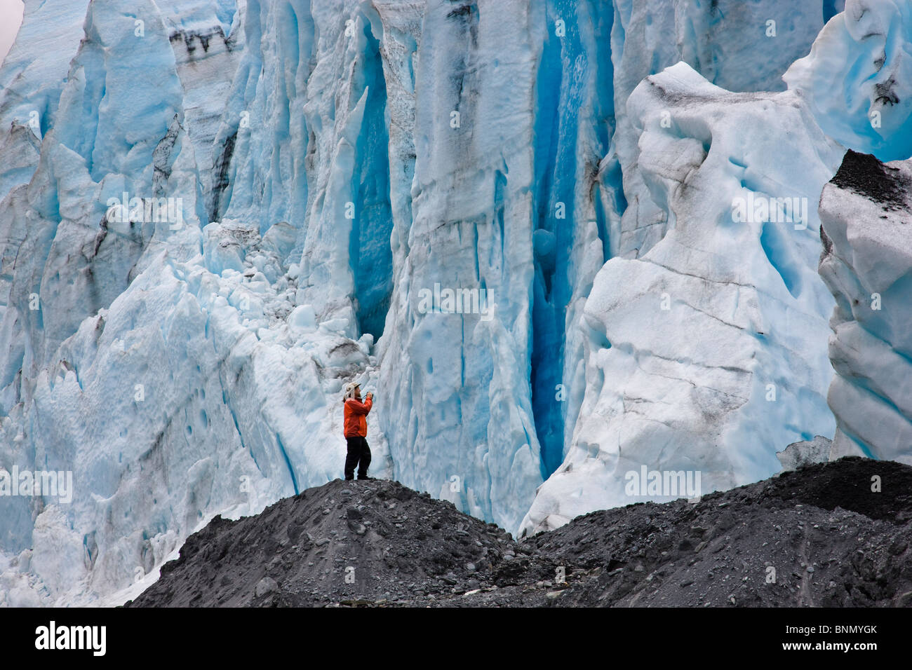 Male photographer standing in front of the tidewater face of Shoup Glacier,  Shoup Bay State Marine Park, Alaska - Stock Image