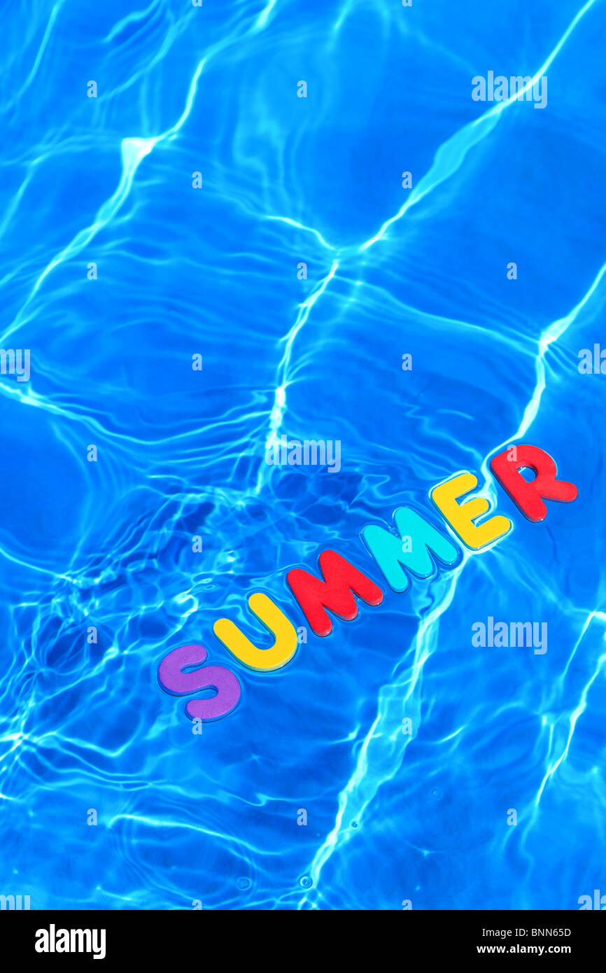 The word SUMMER made from foam letters floating on the water surface of a swimming pool - Stock Image