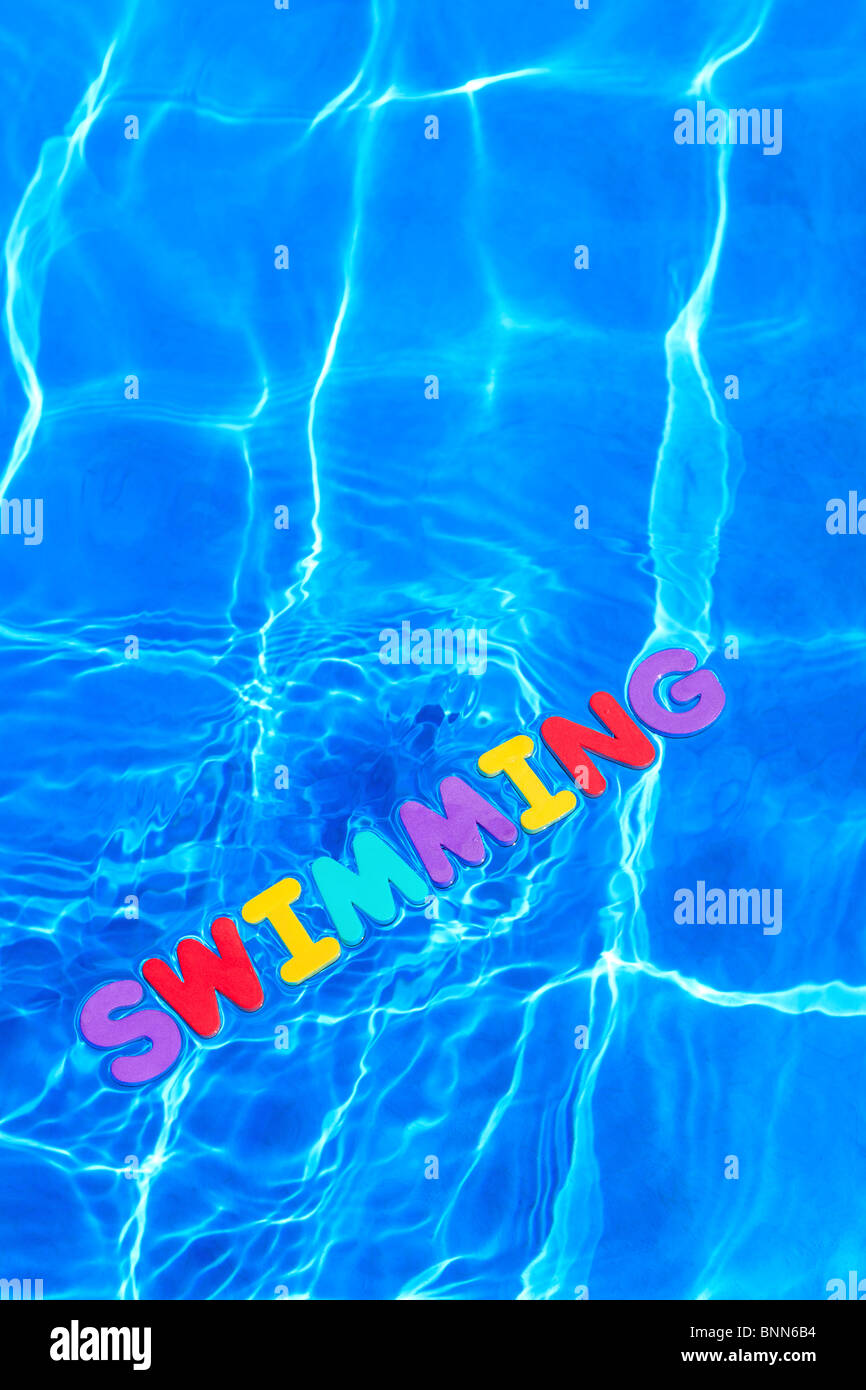 The word SWIMMING made from foam letters floating on the water surface of a pool - Stock Image