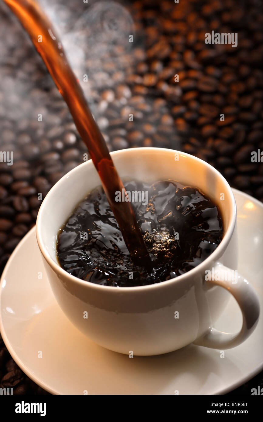 Pouring a cup of traditional steaming hot coffee against coffee-bean background - Stock Image