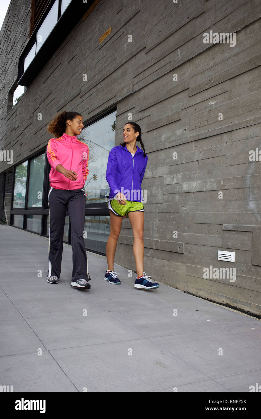 Two girlfriends walking and talking in their running outfits in San Diego. - Stock Image