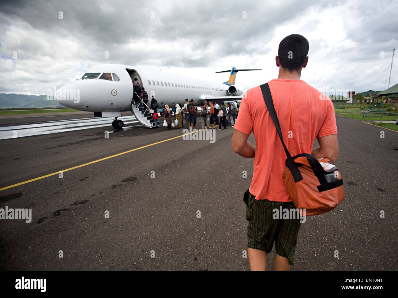 Tall man with shoulder bag walks to airplane. - Stock Image