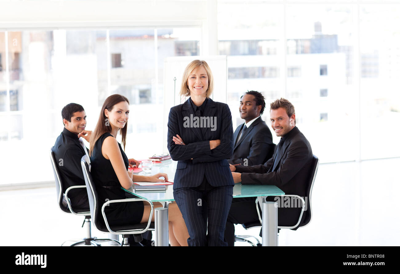 International business team smiling at the camera in a meeting - Stock Image
