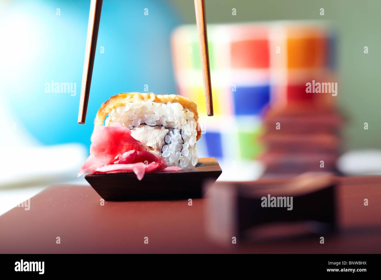 Close-up horizontal photo of the rolled sushi with Philadelphia cheese and tuna on the table and chopsticks - Stock Image
