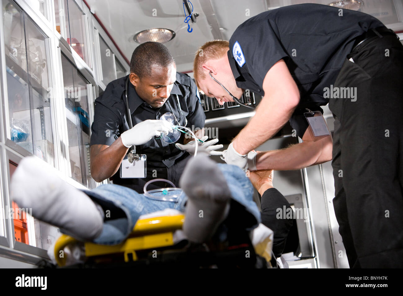 Paramedics caring for patient on stretcher in ambulance - Stock Image