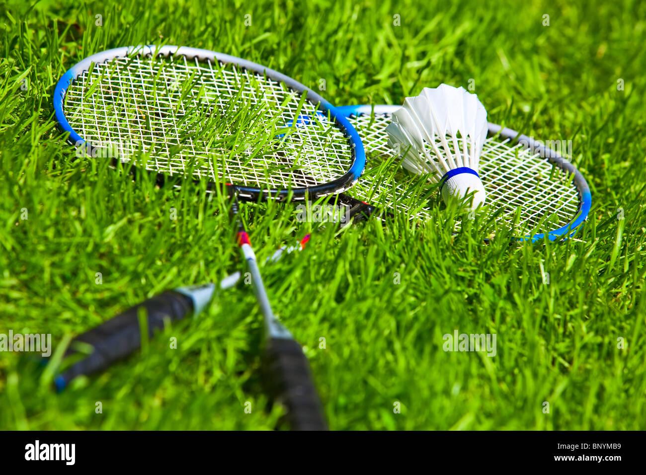 Badminton rackets on green grass. - Stock Image