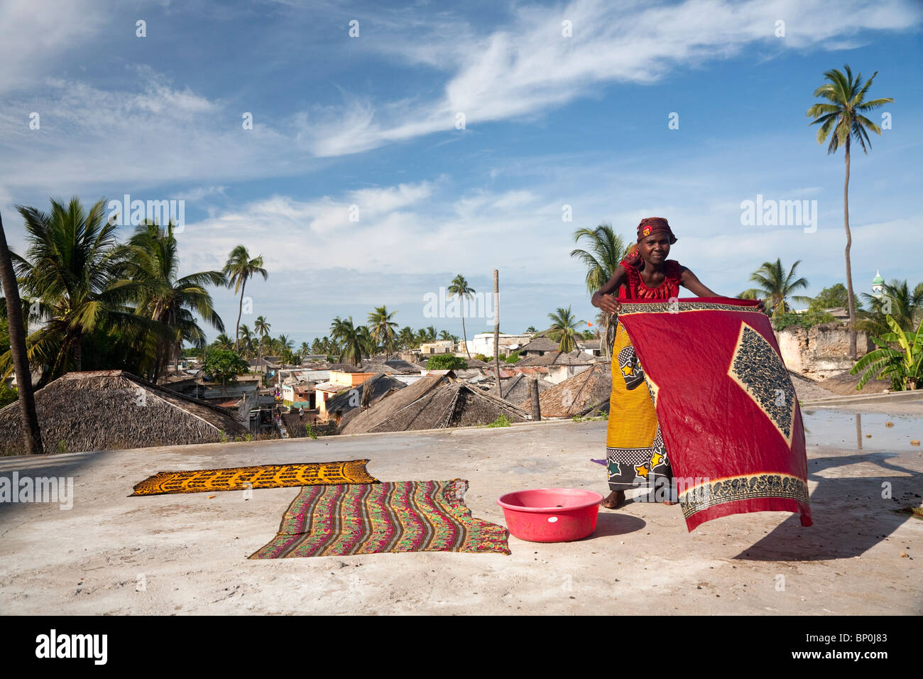 Mozambique, Ihla de Moçambique, Stone Town. A lady dries brightly-coloured Kapolanas on a rooftop in Stone - Stock Image