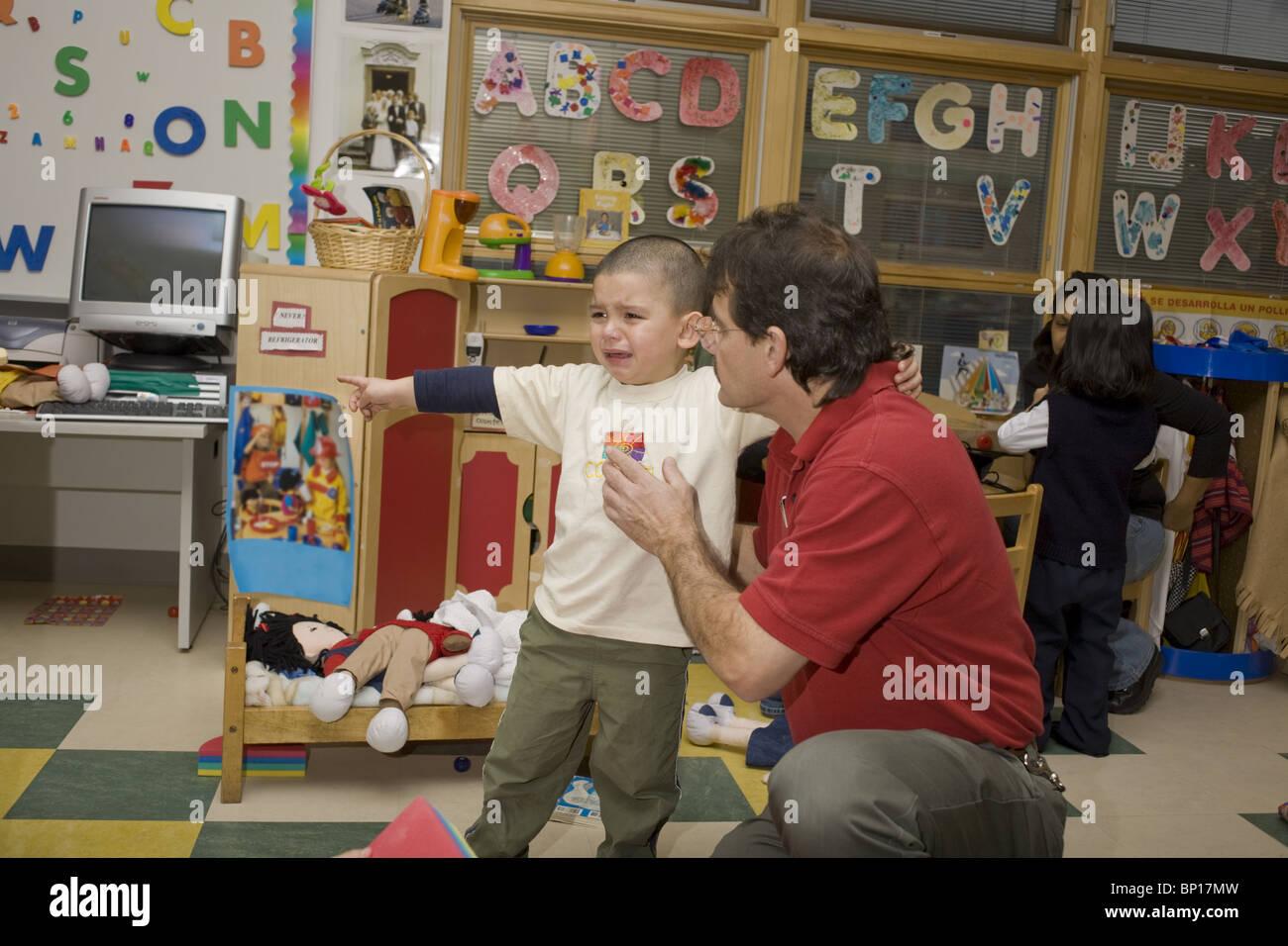 male preschool teacher comforting a crying boy in the classroom BP17MW - Male Kindergarten Teacher