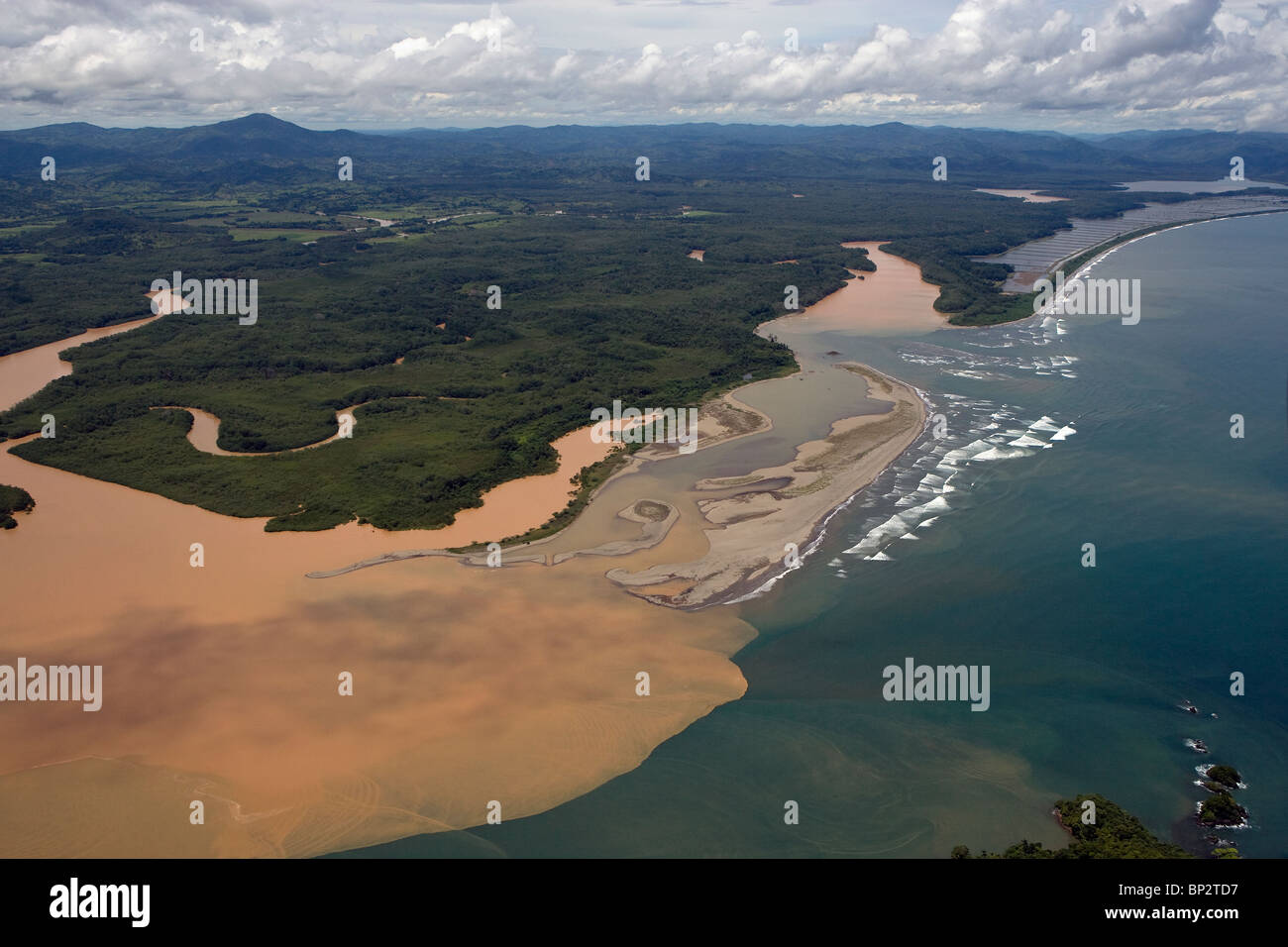 aerial view above sediment filled muddy river flowing into Pacific ocean Republic of Panama - Stock Image