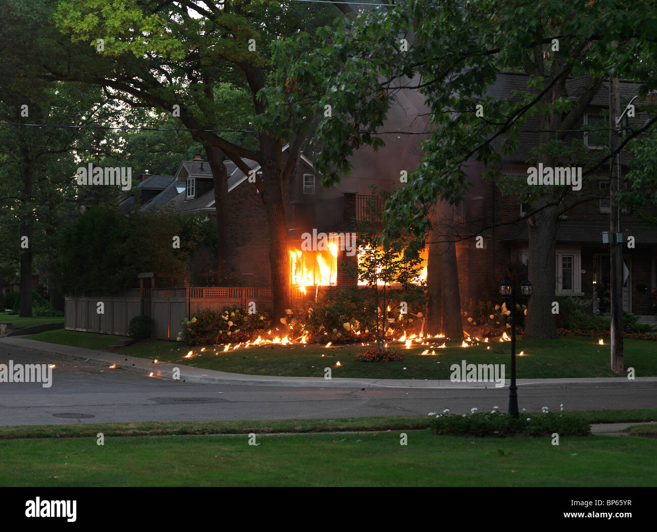 Residential house burning after an explosion - Stock Image