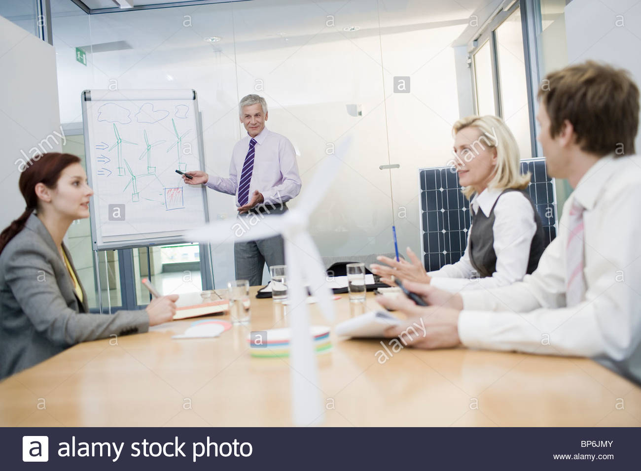 Four businesspeople discussing an alternative energy project - Stock Image