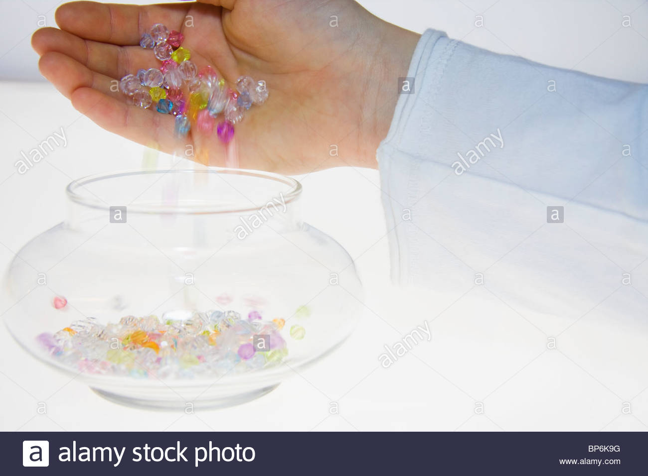 A person pouring colored beads into a jar - Stock Image
