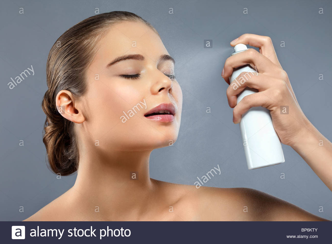 A woman spraying her face with hydrating spray - Stock Image
