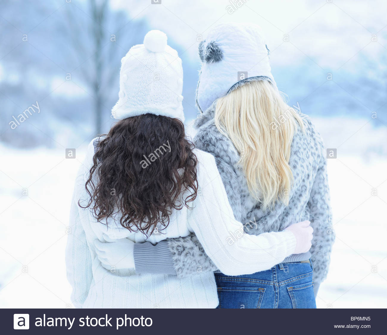 Rear view of two young women hugging on winter day - Stock Image