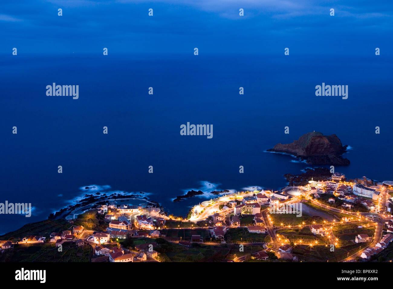 Town and Natural Rock Pools seen from Miradouro da Santinha viewpoint at dusk, Porto Moniz, Madeira, Portugal - Stock Image