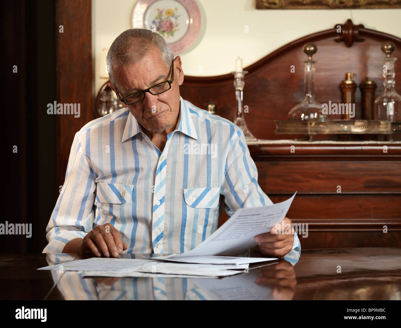 Elderly man sitting at a desk looking through bills with unhappy expression on his face - Stock Image