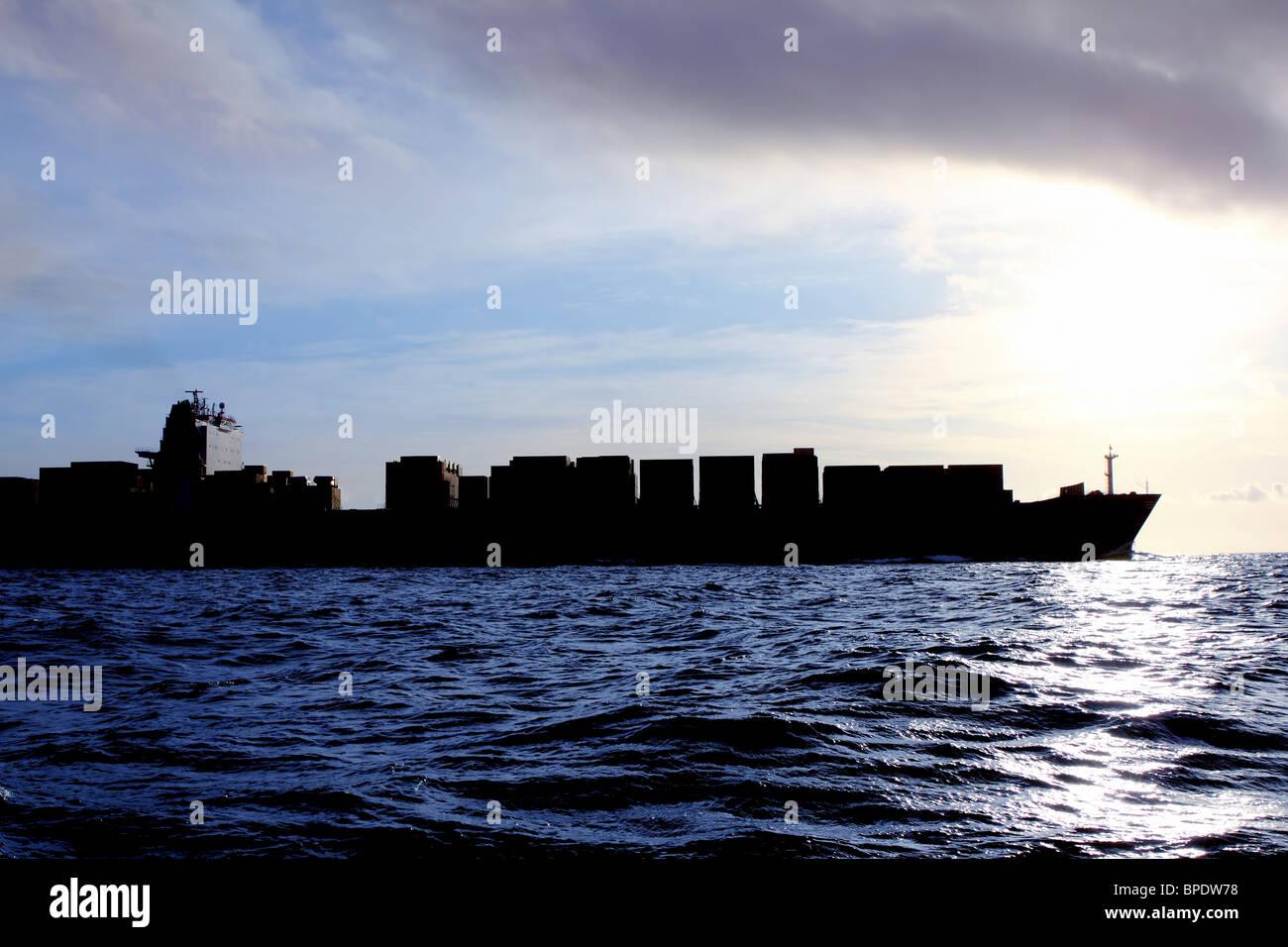 merchant ship cargo back light on sunshine open ocean sea - Stock Image