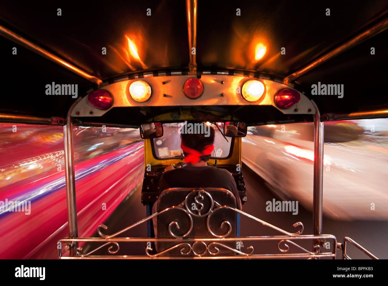 Tuk Tuk or auto rickshaw in motion at night, Bangkok, Thailand, Southeast Asia - Stock Image