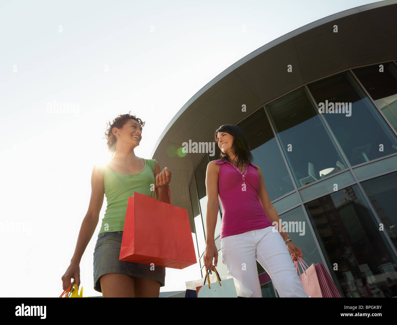 women walking with shopping bags out of shopping center - Stock Image