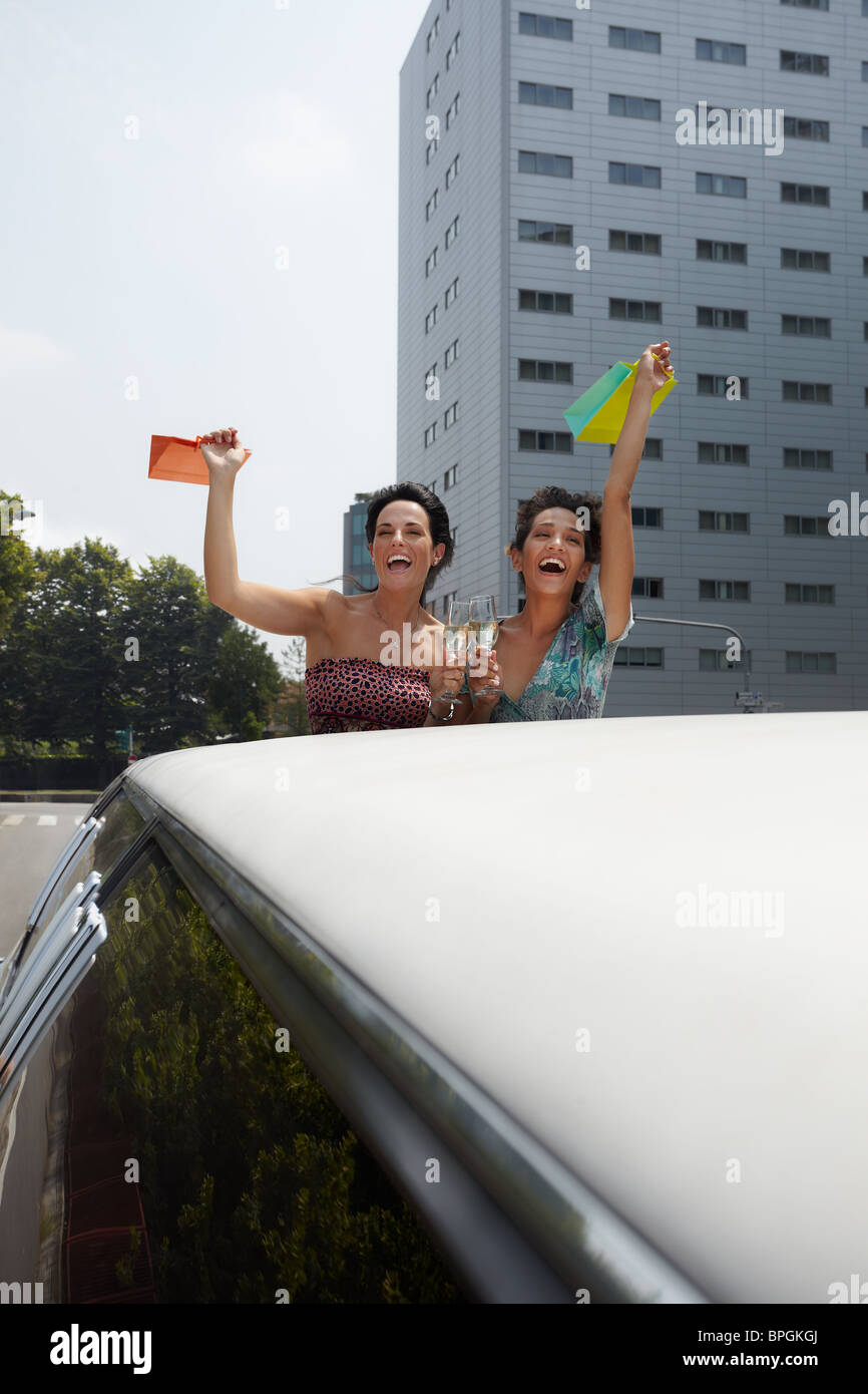 women showing shopping bags on top of limousine - Stock Image