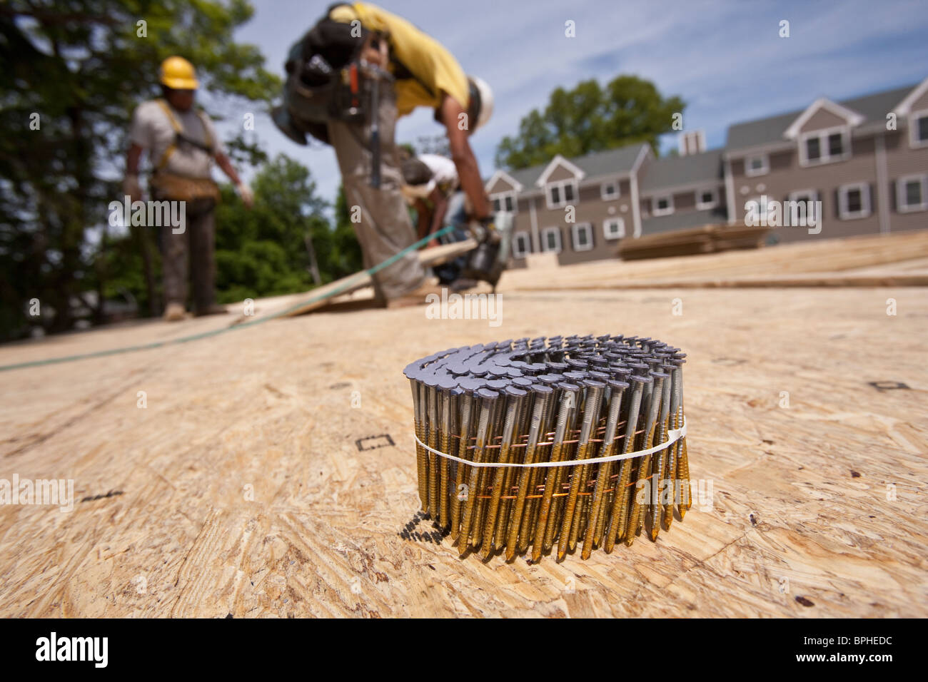 Bundle of nails with a carpenter using nail gun in the background - Stock Image