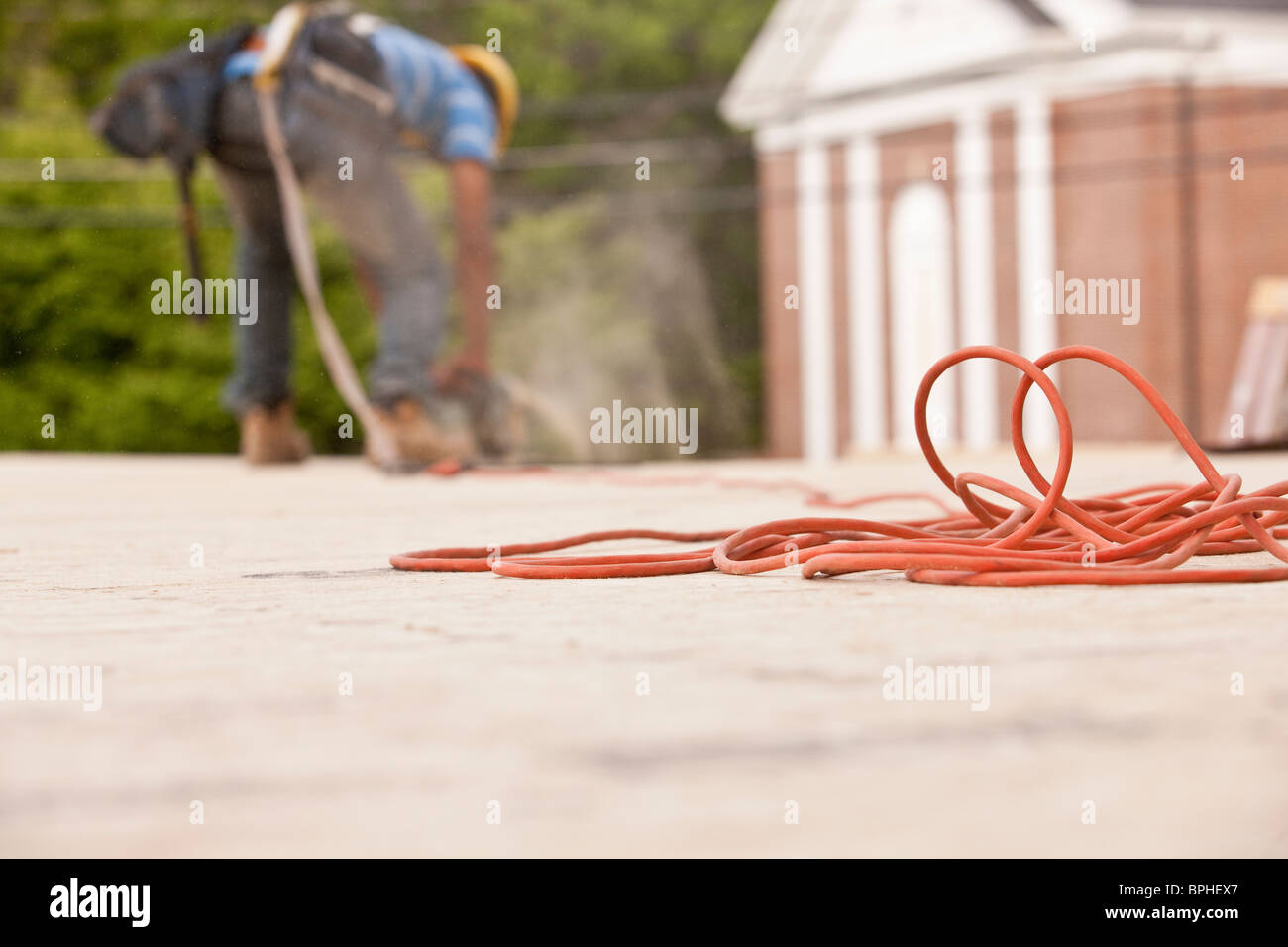 Power cord with a carpenter sawing a board in the background - Stock Image
