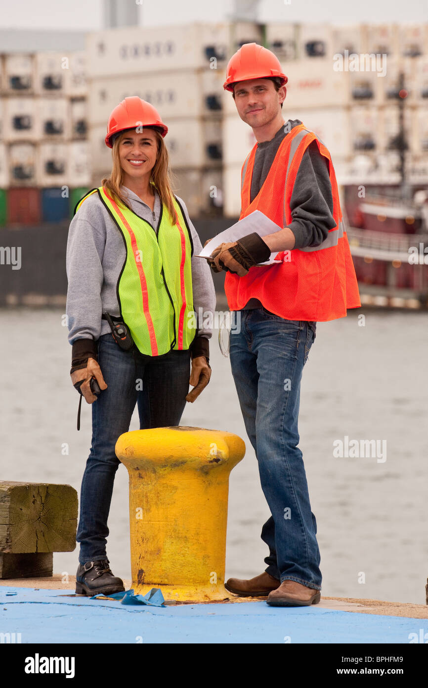 Transportation engineers standing near a bollard on a commercial dock - Stock Image