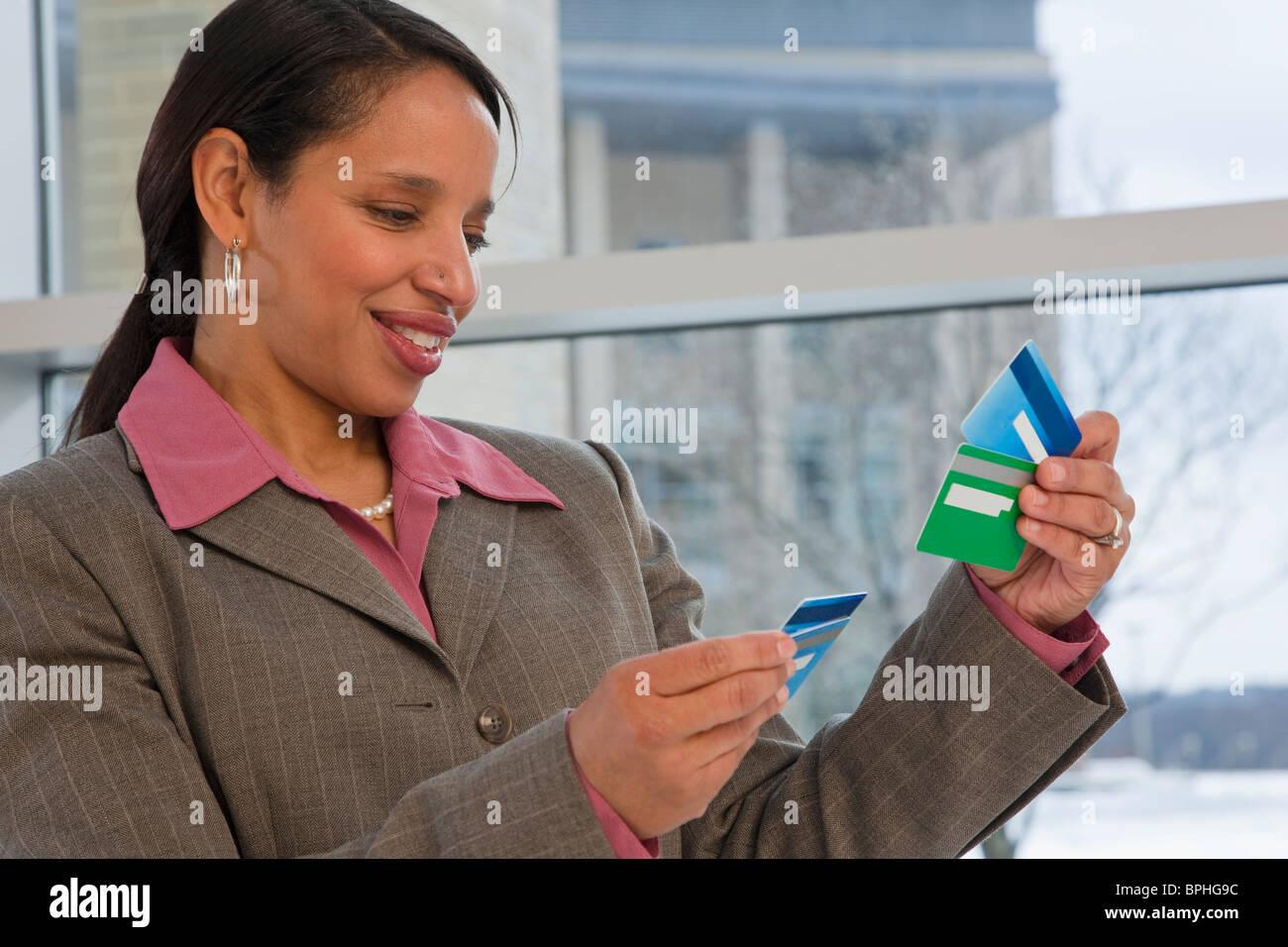Hispanic businesswoman holding credit cards - Stock Image
