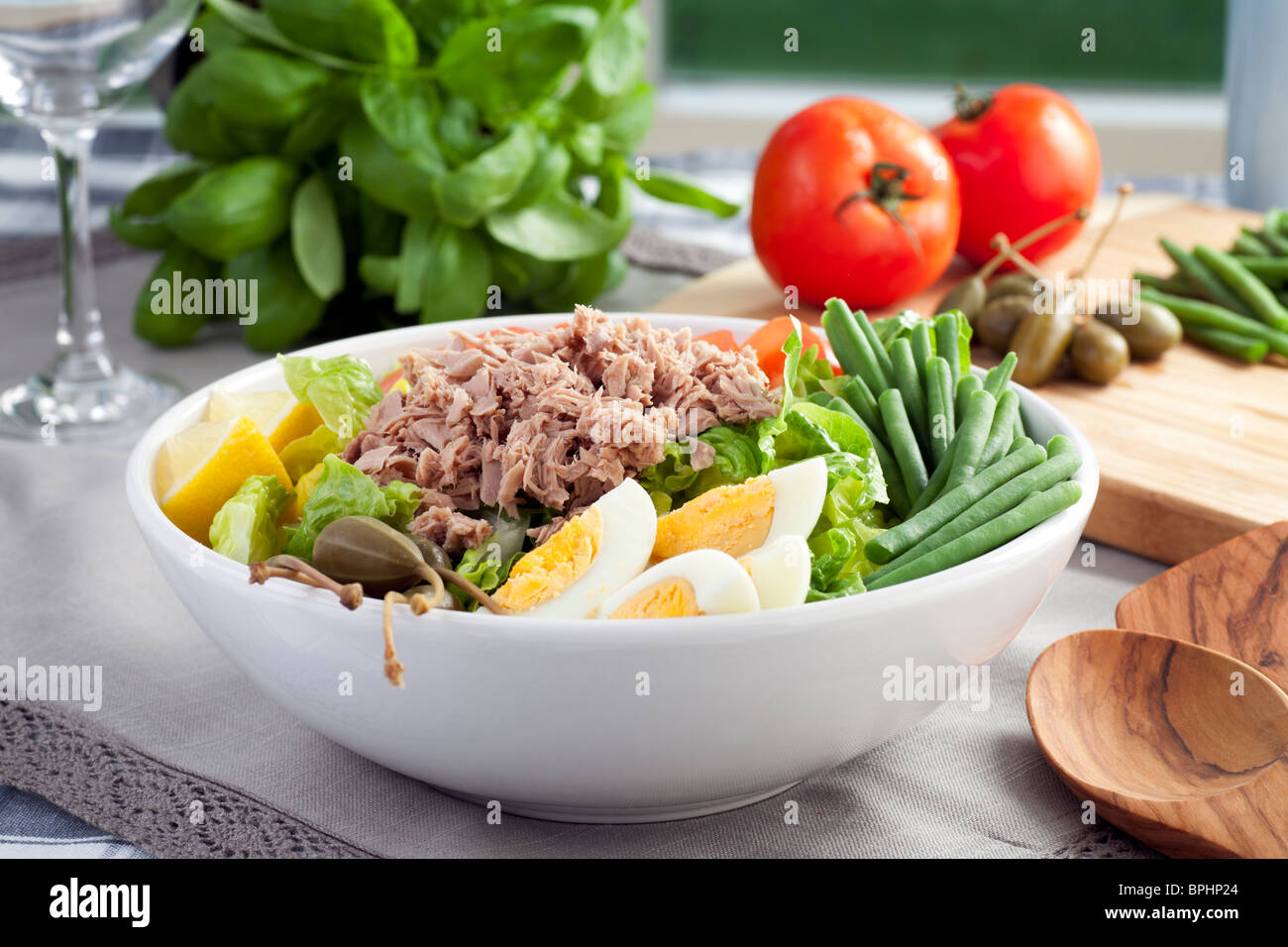 Salad Nicoise with ingredients in background. - Stock Image