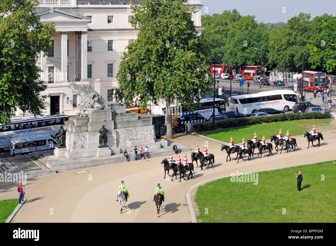 Hyde Park Corner Household Cavalry passing the Royal Artillery Memorial and the Lanesborough Hotel - Stock Image
