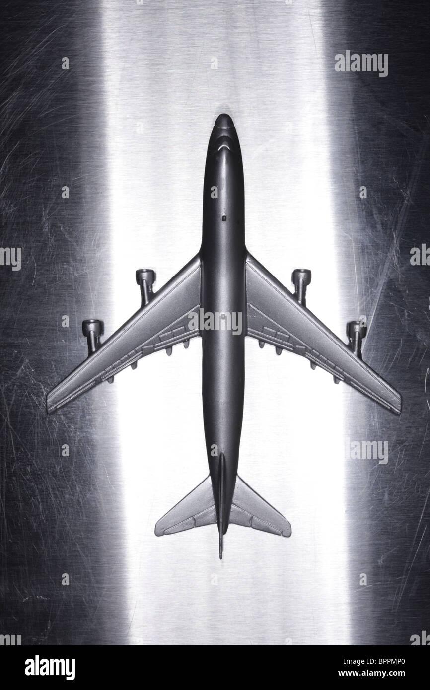 Metal toy airplane on metallic surface - Stock Image