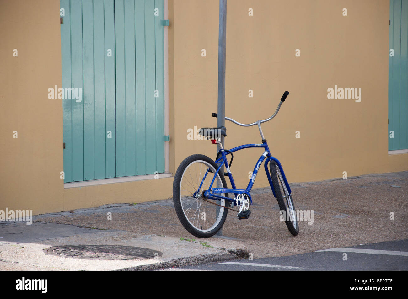 blue bicycle parked on sidewalk - Stock Image
