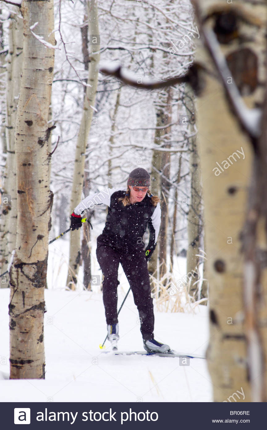 A woman skate skiis on a snowy morning. - Stock Image